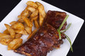 Bbq ribs with potato wedges on a white plate Stock Photography