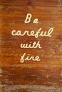Be careful with fire wooden sign an old weathered and worn outdoor carved into it that shows signs of aging Stock Photo