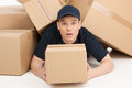 Be careful with fragile deliveryman lying covered with a stack of cardboard boxes and looking at camera Royalty Free Stock Image