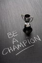 Be a champion the phrase written by hand on used blackboard next to small silver trophy cup might winner or Stock Images