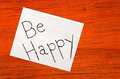 Be happy post it note on wood background Stock Images