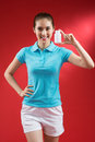 Be healthy vertical portrait of a young sporty woman with a container of vitamins over a red background Stock Image