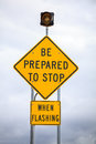 Be prepared to stop when flashing road sign warning Royalty Free Stock Images