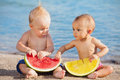 On beach asian baby girl and white boy eat fruits Royalty Free Stock Photo