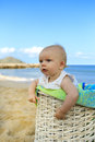 Beach baby in the basket girl white with green towel tropical vacation Royalty Free Stock Photo
