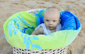 Beach baby in the basket girl white with green towel tropical vacation four months old Stock Images