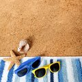 Beach background border sunglasses, towel, starfish, seashell square format sand copy space Royalty Free Stock Photo