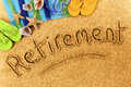 Beach background with towel and flip flops and the words at last written in sand Stock Image