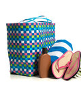 Beach bag with towel flip flops and suntan lotion a a striped pink on a white background Stock Photos