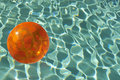 Beach ball floating in pool orange inflatable Stock Photos