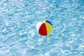 Beach ball floating on surface of swimming pool Royalty Free Stock Images