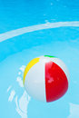 Beach ball in pool clear blue water vacation concept Royalty Free Stock Photos