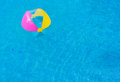 Cute girl playing with beach ball in swimming pool