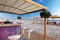 Beach bar summer stand with chairs under the sunblind and huts with lounges on the baltic sea Stock Images