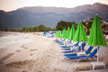 Beach beds and umbrellas in thassos lined up on island Stock Photography