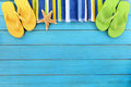 Beach border with blue decking scene striped towel flip flops and starfish on old weathered painted wood space for copy Royalty Free Stock Photos