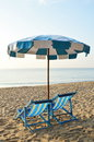 Beach canvas beds with blue and white umbrella Royalty Free Stock Photo