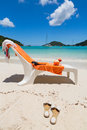 Beach chair with orange towel and coconut drink on beautiful blue lagoon background Stock Images