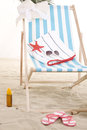 Beach chair in the sand with colorful items Royalty Free Stock Photos
