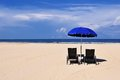 Beach chairs and blue umbrella Royalty Free Stock Photo