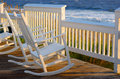Beach chairs sitting on a porch in front of the ocean Royalty Free Stock Photo