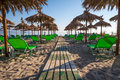 Beach chairs with umbrellas tropical sandy green and palm Stock Photos