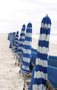 Beach chairs and unbrellas blue white umbrellas posted on a waiting for customers Stock Image