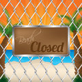 Beach closed sign on wired fence with sunset in background Royalty Free Stock Images