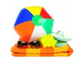 Beach collection ball sunglasses and flip flops on orange towel over white Royalty Free Stock Images