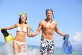 Beach couple fun in water laughing snorkeling having with fins together smiling happy and joyful summer holidays travel lifestyle Royalty Free Stock Photo