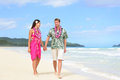Beach couple on hawaii vacation with hawaiian leis happy walking and aloha clothing caucasian men wearing typical Royalty Free Stock Images