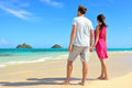 Beach couple looking at ocean view from behind standing on white sand in pink dress and beachwear on vacations on lanikai Stock Images