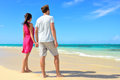Beach couple looking at ocean view from behind unrecognizable standing on white sand in pink dress and casual shorts Stock Photos