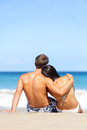 Beach couple romantic in love relaxing on travel enjoying ocean view together sitting the sand embracing and hugging beautiful Stock Photos