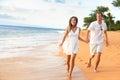 Beach couple on romantic travel honeymoon fun walking having running vacation summer holidays romance young happy lovers asian Royalty Free Stock Photography