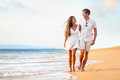 Beach couple walking on romantic travel honeymoon vacation summer holidays romance young happy lovers asian women and caucasian Stock Image