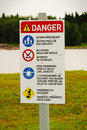A beach danger sign with rules in both english and french Royalty Free Stock Photo