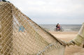 Beach fence decorated net cyclists going near sea Royalty Free Stock Photo