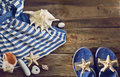 Beach flip flops striped dress seashells on a wooden floor summer vacations background Royalty Free Stock Images