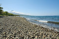 Beach in flores island stony with volcano at background indonesia Royalty Free Stock Photo
