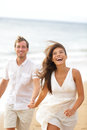Beach fun couple laughing and running together during summer travel vacation holiday on beautiful golden joyful excited Royalty Free Stock Images
