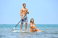 Beach fun couple on stand up paddleboard surfboard surfing together in ocean sea big island hawaii beautiful young multi ethnic Stock Photo