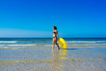 Beach girl walking along the seashore enjoying free time with yellow float in cadiz atlantic ocean Stock Images