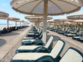 Beach in hotel chairs and sunshades on mediterranean sand Royalty Free Stock Photo