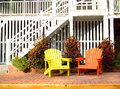 Beach house with colorful wooden chairs a pair of adirondack one yellow and one orange in front of a white Stock Image