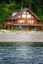 Beach house view of a log island with a large deck lots of glass and a wide front porch standing just steps from the water edge a Stock Photo