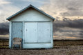 Beach hut on cloudy day a a with an empty chair in front of it Stock Photos