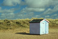 Beach hut in the dunes a single colorful stands amongst sand Royalty Free Stock Photo