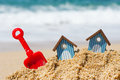 Beach huts and toys miniature with red plastic shovel Stock Photos