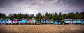 Beach huts at wells next the sea norfolk england positioned along the tree line on this populat sandy in panoramic image Stock Photography